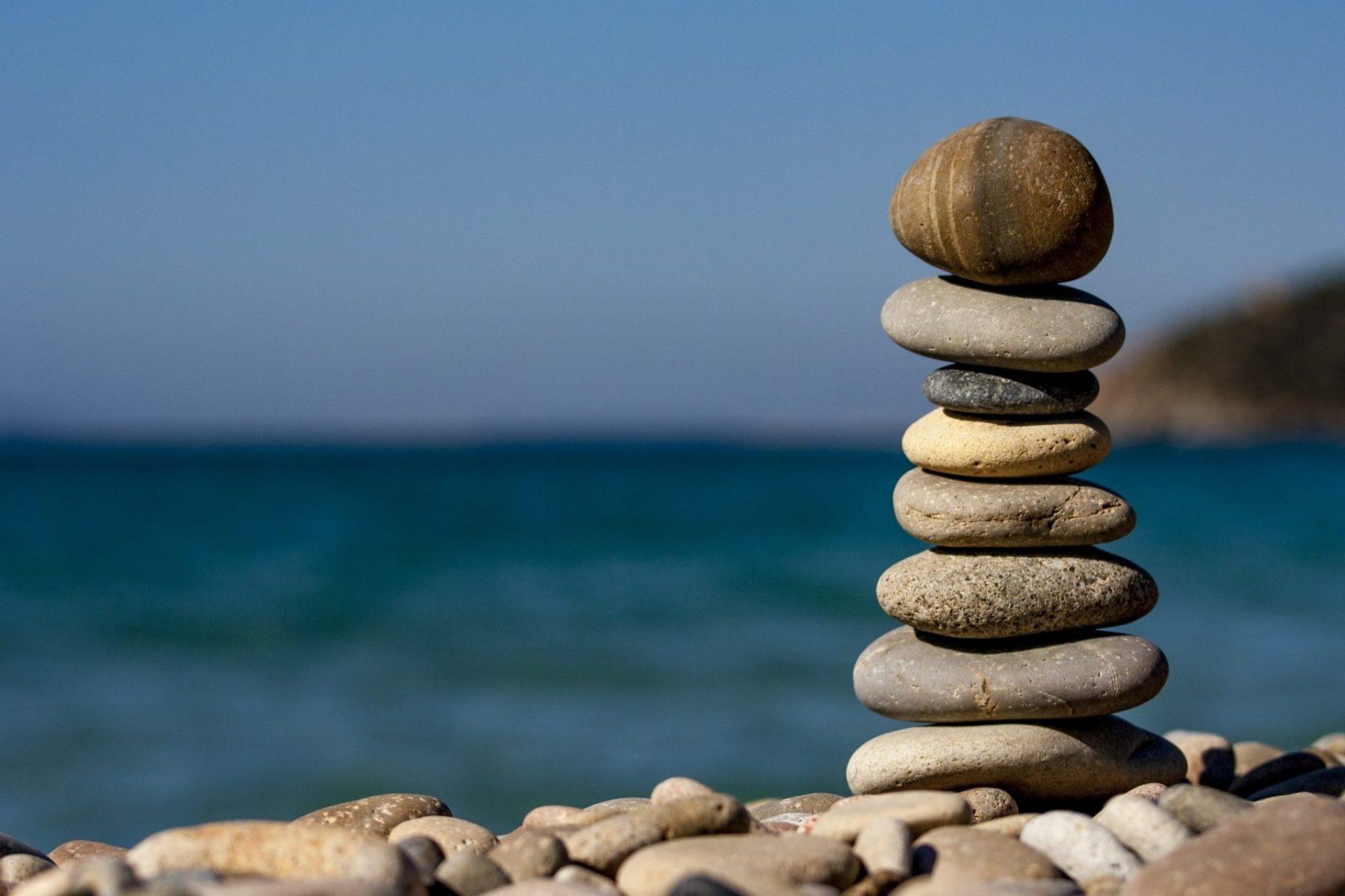 Steine balancieren sich vor einem Strand gegenseitig aus